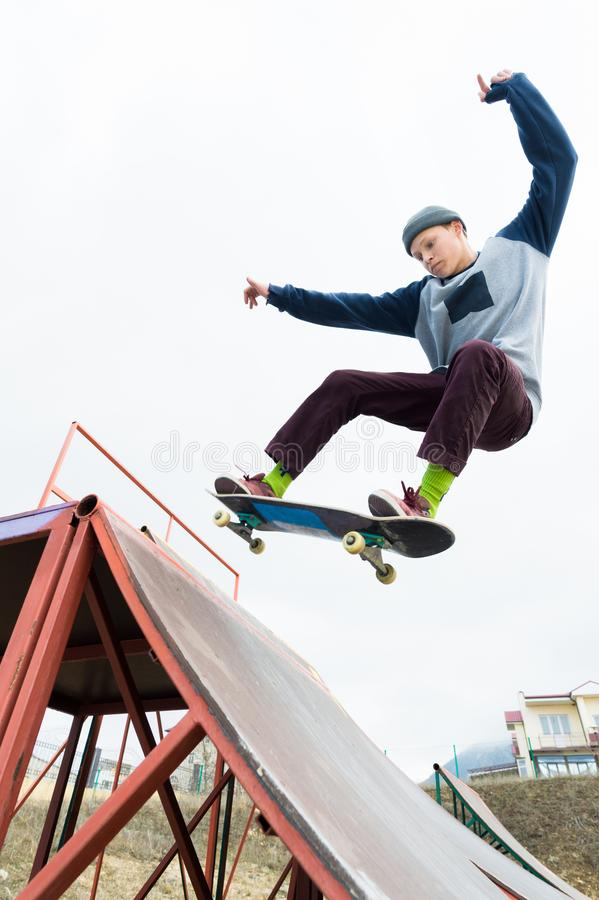 A skateboarder teenager in a hat does a trick with a jump on the ramp. A skateboarder is flying in the air stock photography