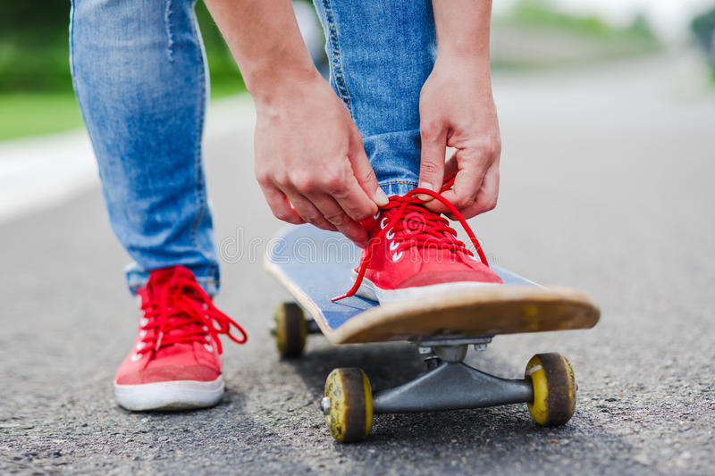 Skateboarder tying shoelace at city road stock images