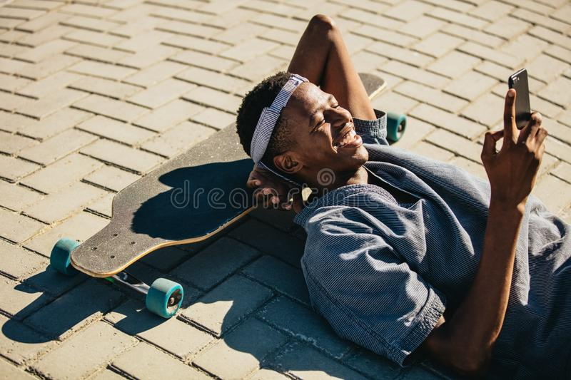 Skateboarder using smart phone stock photography