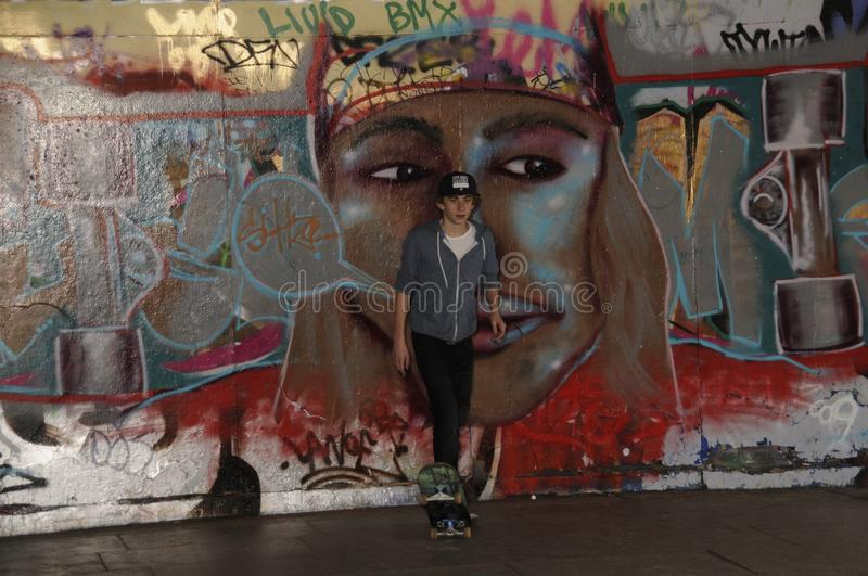 Skateboarder waiting his turn to have a go. Male skateboarder standing against a wall coloured with a colourful graffiti depicting the face of a young male with royalty free stock photos