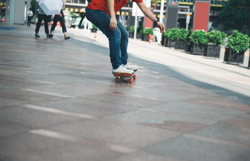 Skateboarderbenen die skateboard berijden op stadsstraat royalty-vrije stock foto