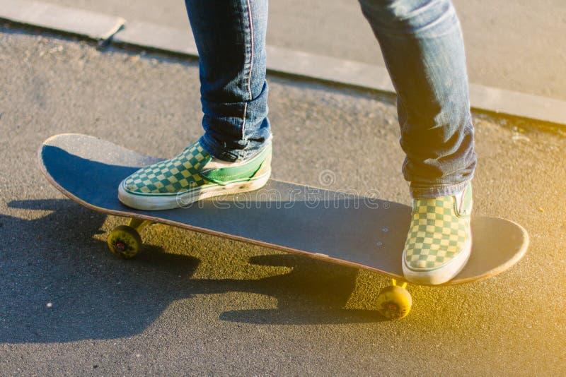 Skateboarderflicka` s lägger benen på ryggen i gymnastikskor som utomhus gör ett trick på skateboarden arkivfoto