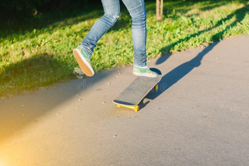 Skateboarderflicka` s lägger benen på ryggen i gymnastikskor som utomhus gör ett trick på skateboarden royaltyfri foto