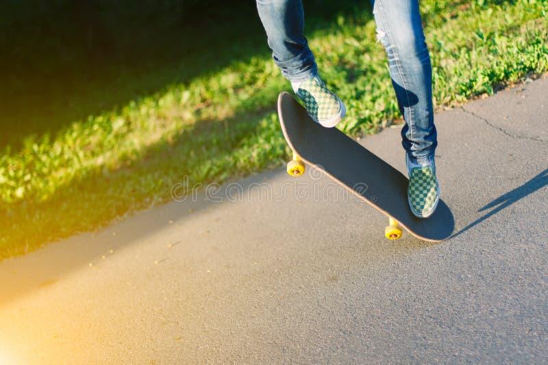 Skateboarderflicka` s lägger benen på ryggen i gymnastikskor som utomhus gör ett trick på skateboarden arkivbild