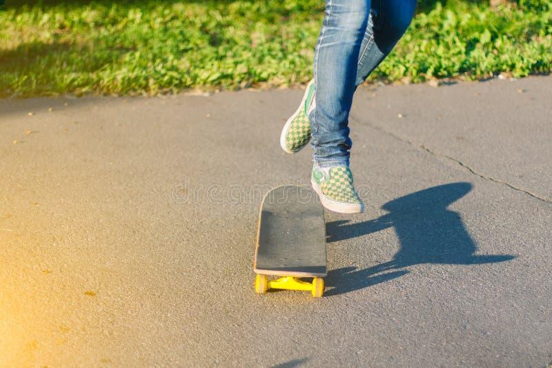 Skateboarderflicka` s lägger benen på ryggen i gymnastikskor som utomhus gör ett trick på skateboarden royaltyfri fotografi
