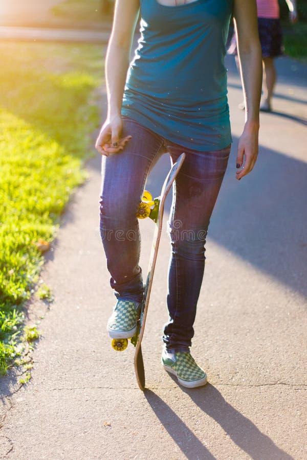 Skateboarderflicka` s lägger benen på ryggen i gymnastikskor som utomhus gör ett trick på skateboarden royaltyfria bilder