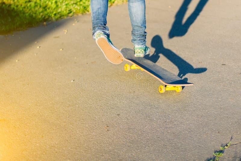 Skateboarderflicka` s lägger benen på ryggen i gymnastikskor som utomhus gör ett trick på skateboarden fotografering för bildbyråer