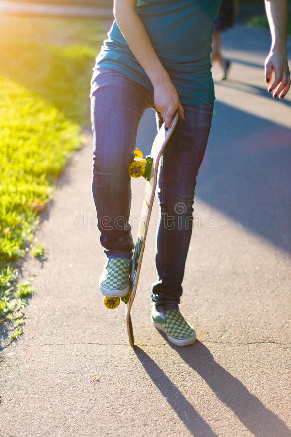 Skateboarderflicka` s lägger benen på ryggen i gymnastikskor som utomhus gör ett trick på skateboarden arkivfoton