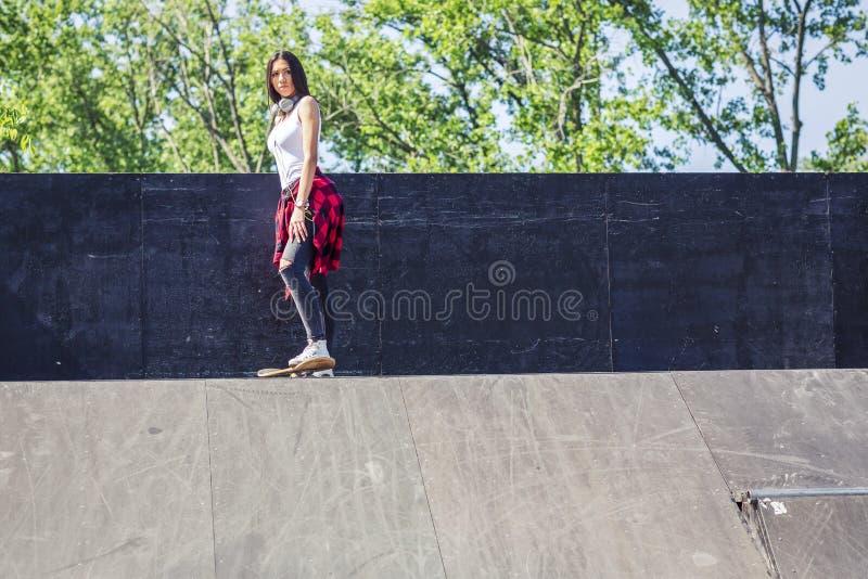 Skateboarderflickan som skateboarding p? skridskon, parkerar royaltyfri foto
