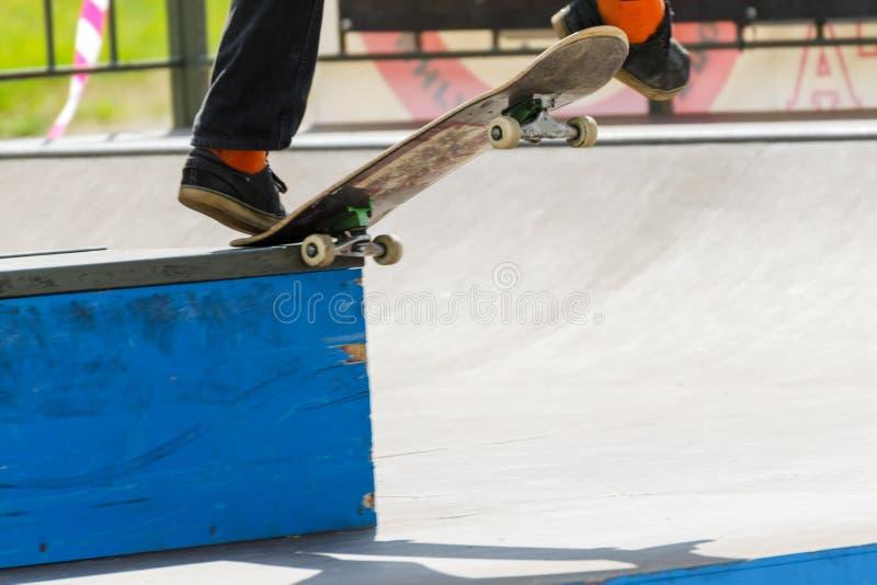 Skateboardfahrer auf Fahrten eines Skateboards auf eine Steinbeschränkung das Skateboard fahren des Wettbewerbs führt Trick durch lizenzfreie stockbilder