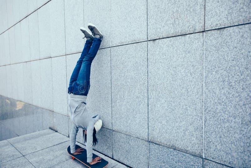 Skateboardfahrer, der eine Hand auf Skateboard gegen Wand tut stockbilder