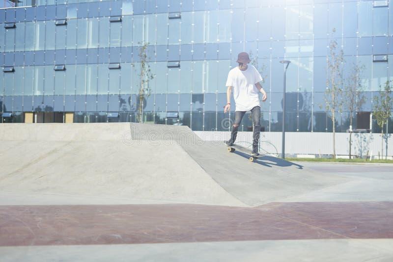 Skateboardfahrer, der einen Trick in einem Rochenpark, Praxisfreistil-Extremsport tut stockbilder