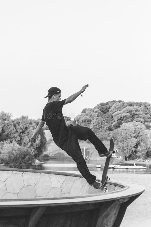 Skateboardfahrer, der einen Trick in Schwarzweiss tut stockbilder