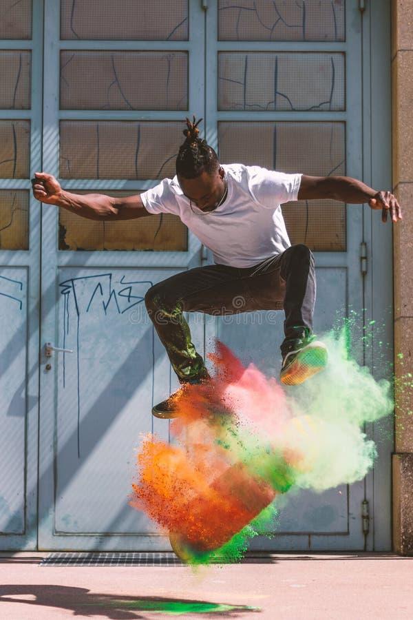 Skateboardfahrer, der kickflip mit buntem holi Pulver tut stockfotos
