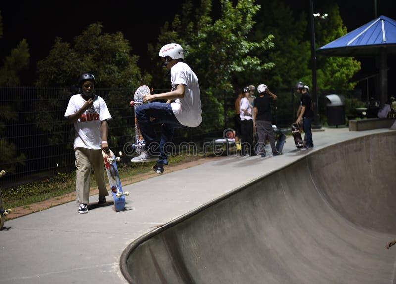 Skateboardfahrer, der Trick am skatepark tut stockfotografie