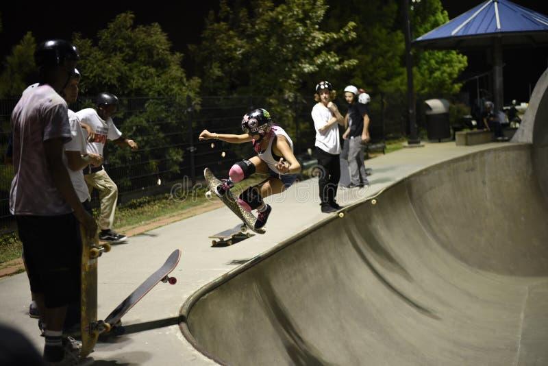 Skateboardfahrer, der Trick am skatepark tut stockfoto