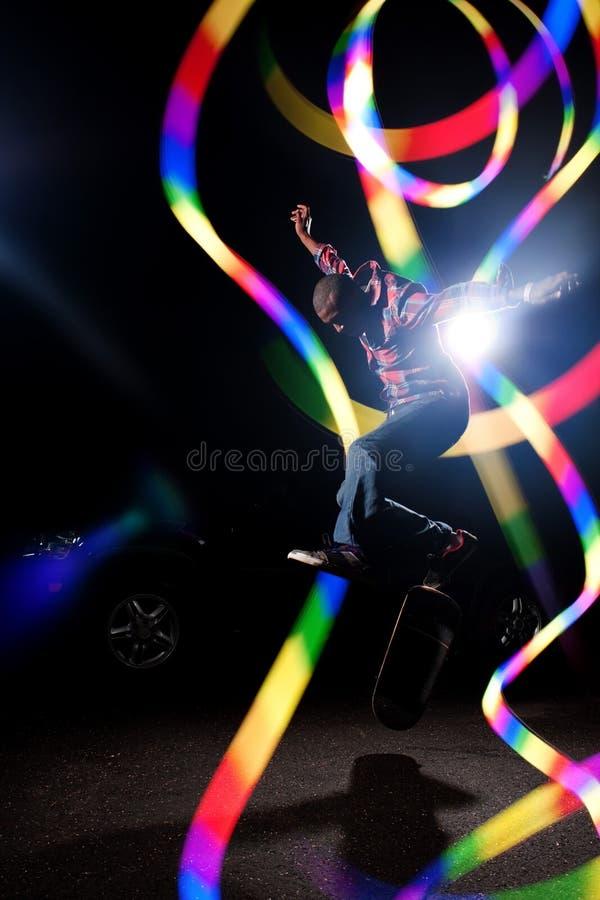 Skateboardfahrer mit abstrakter Leuchte stockfotografie
