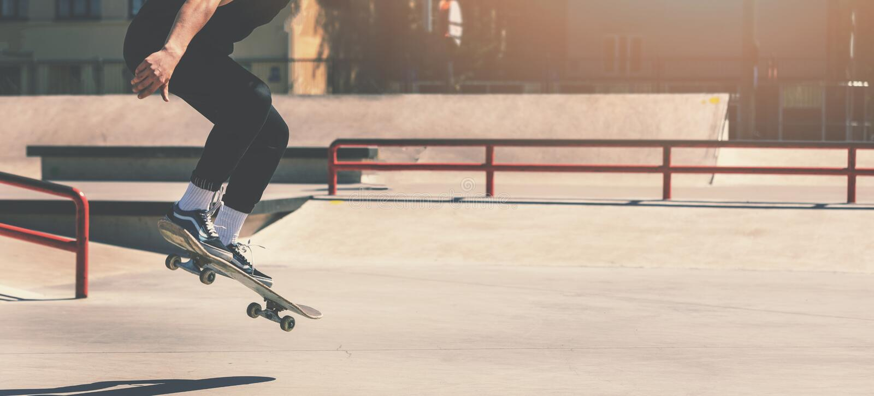 Skateboarding - скейтбордист делая фокус скача на парк конька города стоковые фотографии rf