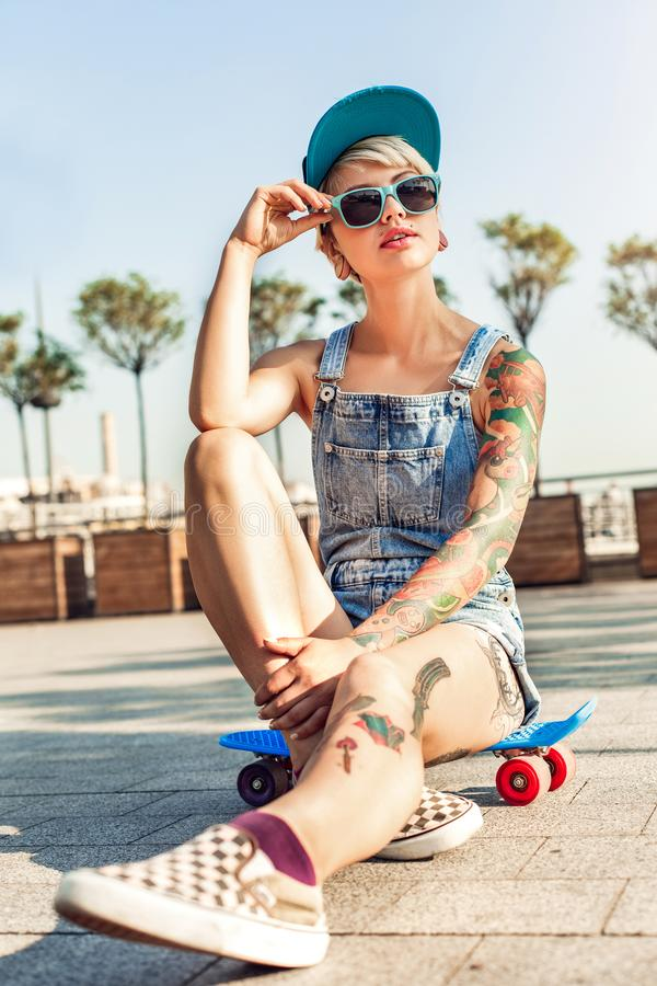 Skateboarding. Alternative girl skater in cap and sunglasses sitting on penny board on the city street looking aside stock image
