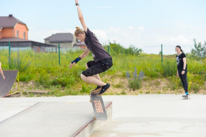 Skateboarding contest in skate park of Pyatigorsk.Young Caucasian skateboarders riding in outdoor concrete skatepark stock images