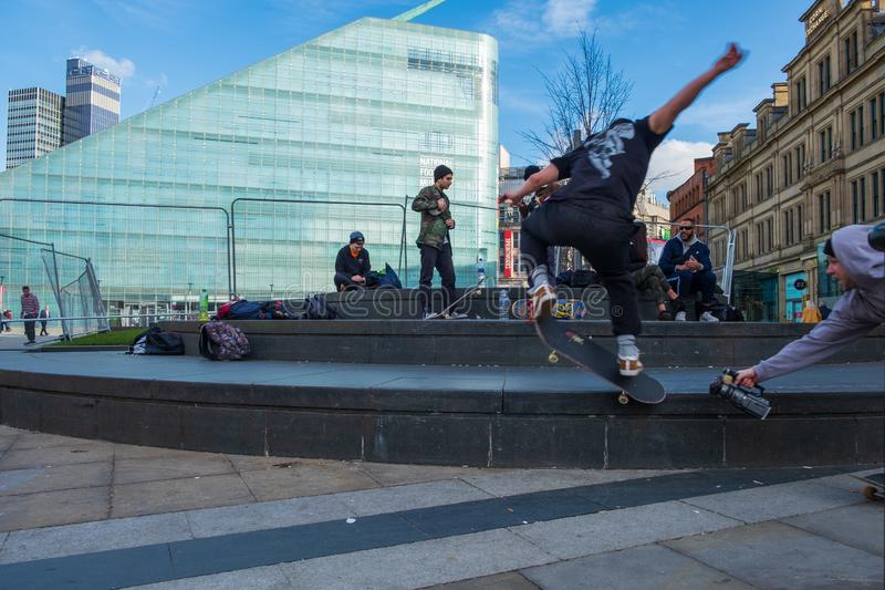 Skateboarding e vídeo dos adolescentes que filmam um outro na frente do museu nacional do futebol no centro de Manchester City imagens de stock royalty free