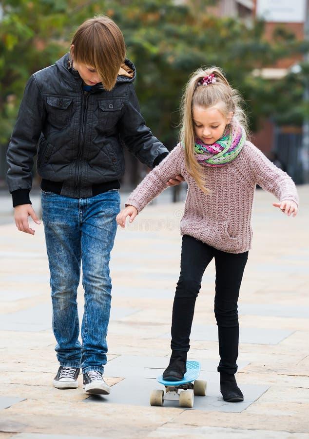 Skateboarding för tonåringundervisningsyster royaltyfria bilder
