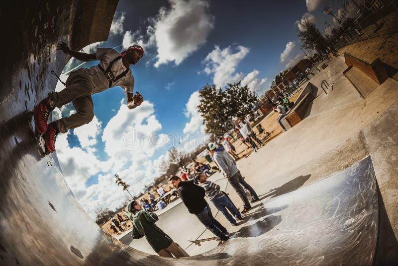 African American Male Rollerblading at skatepark stock image