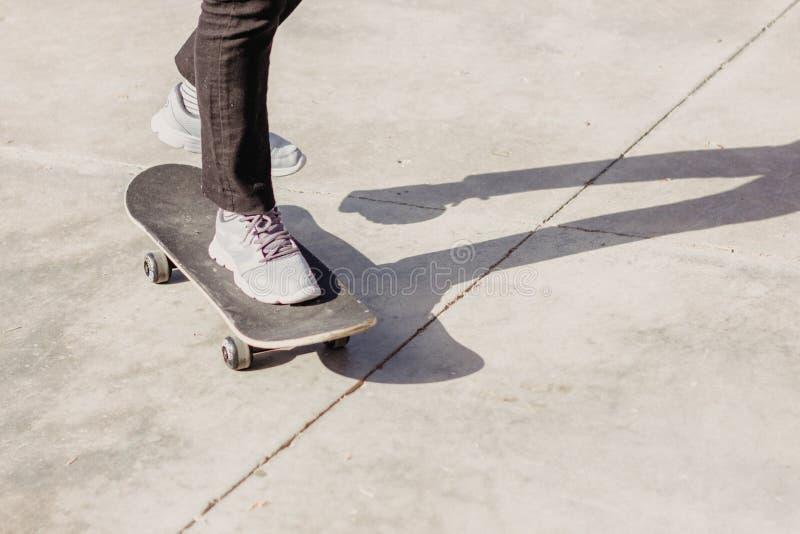 Skateboarding Piernas en jeans y zapatillas en patineta foto de archivo