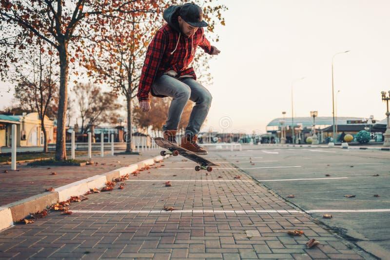 Skateboarding Un hombre hace una maniobra de Ollie en una patineta Saltar al aire Calle al fondo foto de archivo