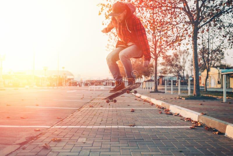 Skateboarding Un hombre hace una maniobra de Ollie en una patineta Saltar al aire Calle al fondo Luz solar imagen de archivo libre de regalías
