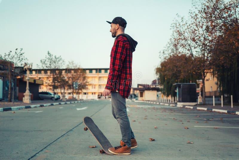 Skateboarding Un hombre posa con una tabla de patinaje Calle al fondo imagenes de archivo
