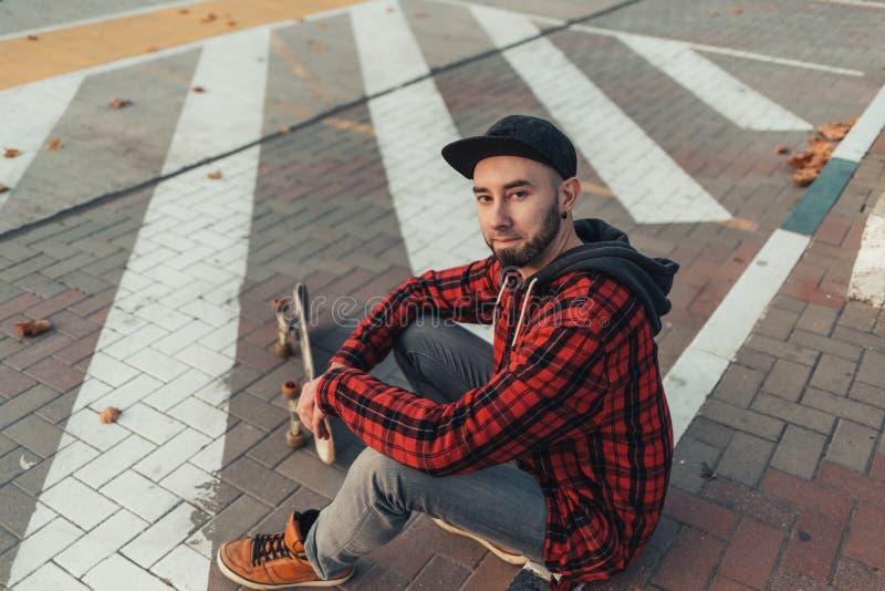Skateboarding Un joven con una gorra negra, jeans y una camisa de manta roja se sienta en una patineta La vista desde arriba fotos de archivo