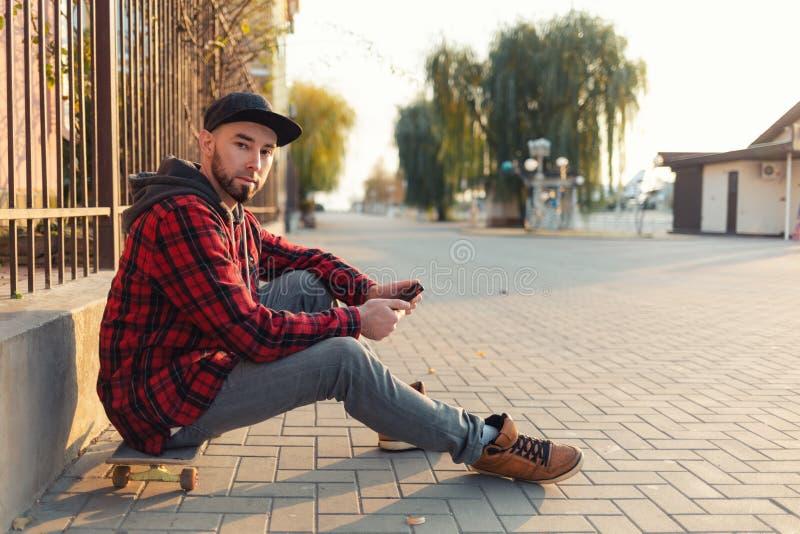 Skateboarding Un joven sentado en una patineta, con un smartphone en las manos El hombre lleva una gorra negra, jeans y un rojo foto de archivo