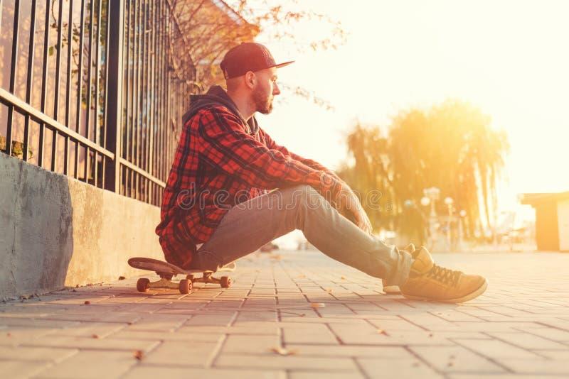 Skateboarding Un tipo guapo con barba, con una gorra y ropa de moda posa con un patín en las calles de la ciudad imágenes de archivo libres de regalías