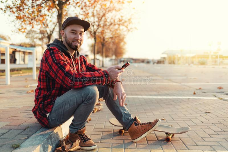 Skateboarding Un tipo guapo con barba y ropa de moda, sentado en la acera con un smartphone en las manos En su fotografía de archivo libre de regalías