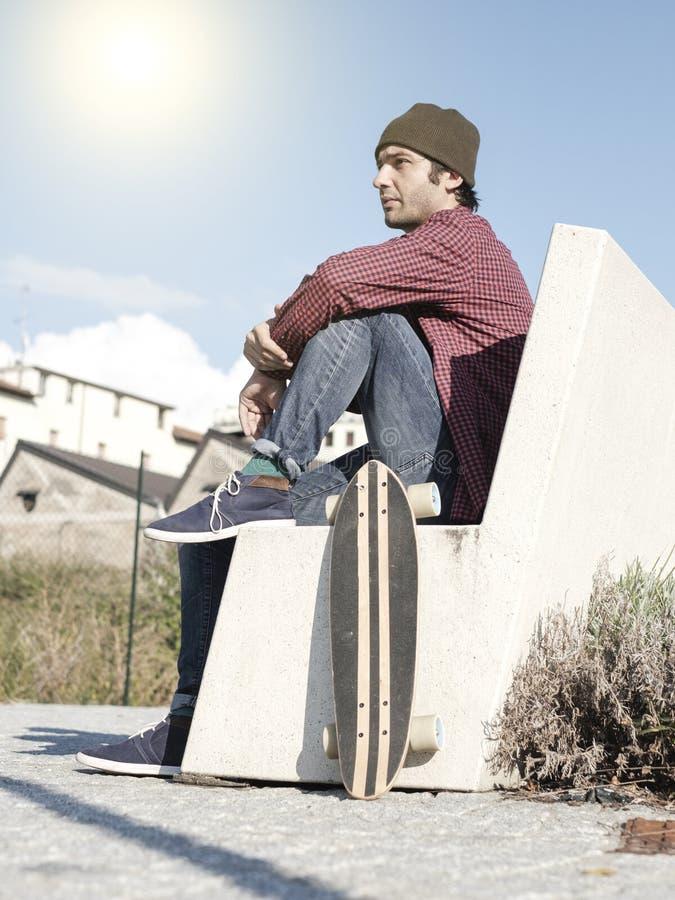 Skateboradåkare och hans skridsko i staden royaltyfri foto