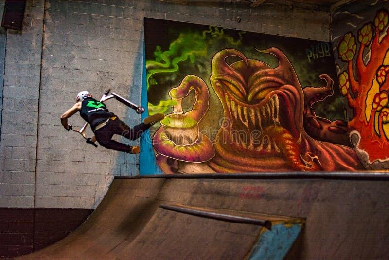 Skateboradåkare på en sparkcykel royaltyfri bild