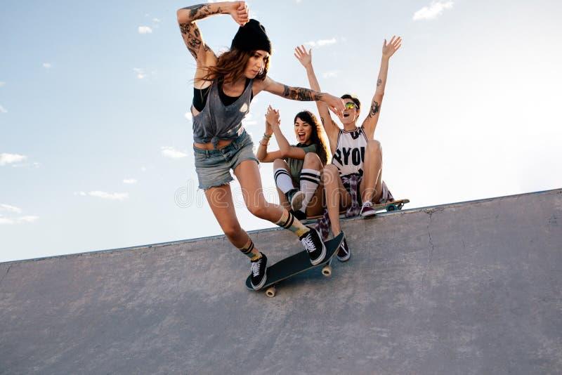 Skateboradåkareflickan rider på skateboarden på skridskon parkerar fotografering för bildbyråer