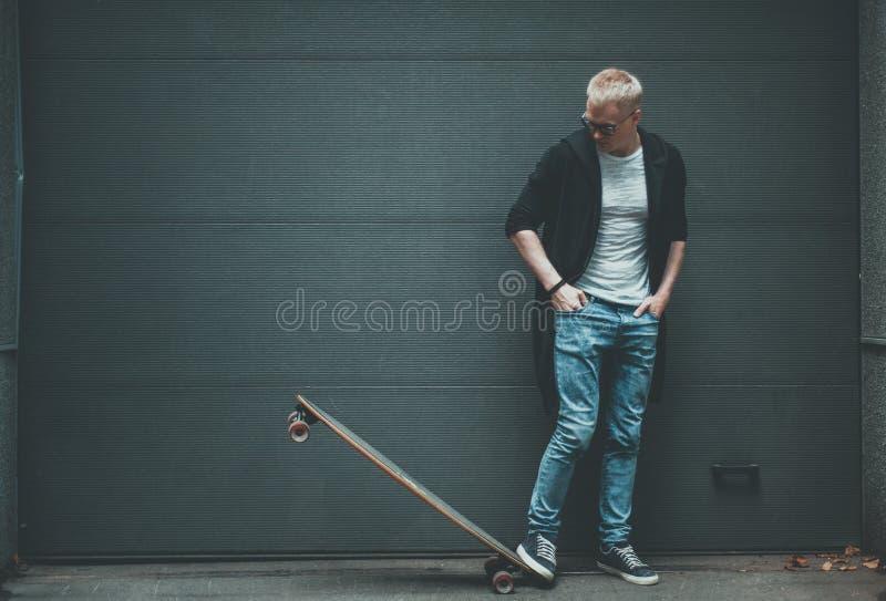 Skateboradåkaren för den unga mannen står med det långa brädet royaltyfri fotografi