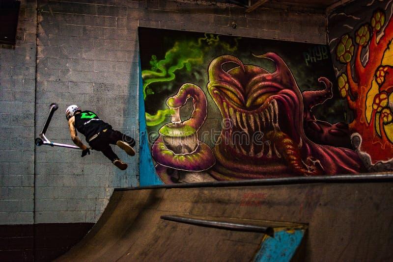 Skateboradåkaren på en skridsko parkerar på sparkcykeln fotografering för bildbyråer