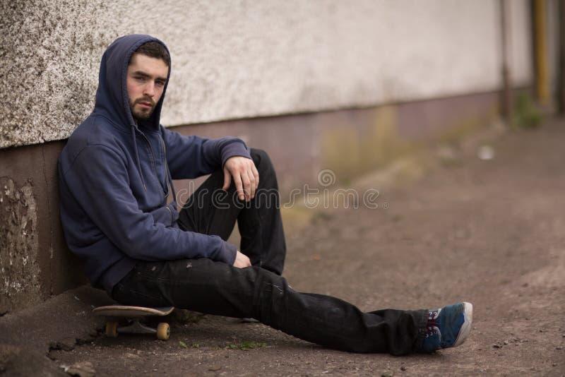 Skateboradåkaren som tar ett avbrott utanför skridskon, parkerar och ser kameran fotografering för bildbyråer