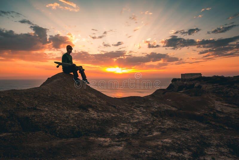 Skateboradåkarepojke på solnedgången royaltyfria bilder