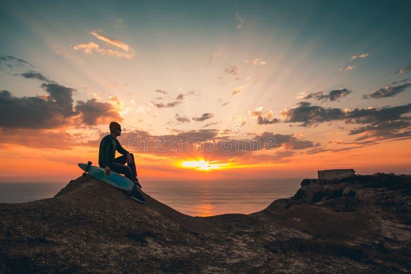 Skateboradåkarepojke på solnedgången arkivbilder