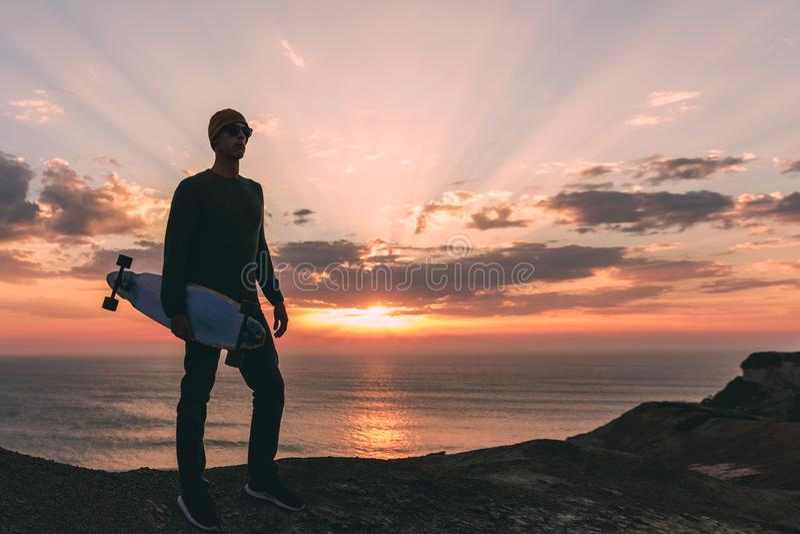 Skateboradåkarepojke på solnedgången arkivfoto
