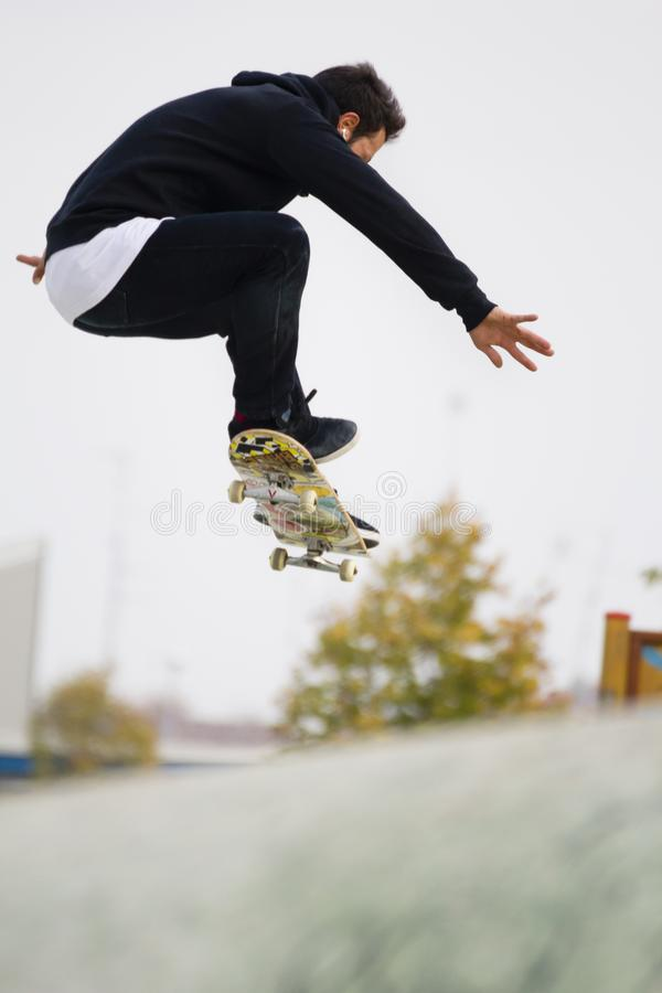 Skateboradåkarepojken hoppar med skridskon royaltyfri bild