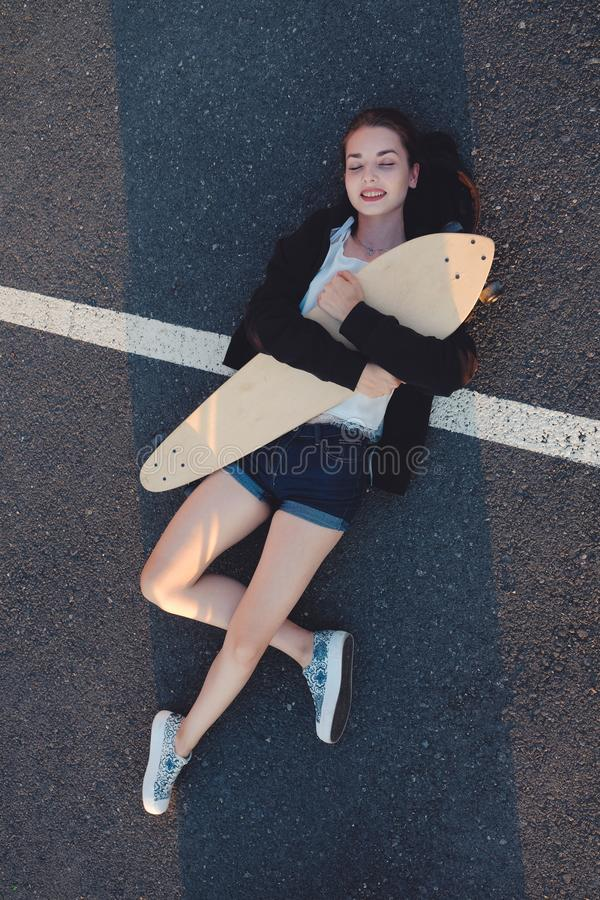 Skateg-Mädchen, das sich mit ihrem longboard auf Asphaltstraßenoberfläche hinlegt stockfotos