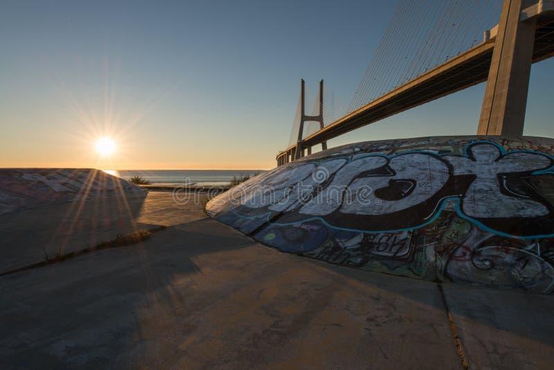 Skatepark em Vasco de Gama Bridge em Lisboa durante o nascer do sol Parque subterrâneo do patim em Ponte Vasco de Gama imagens de stock royalty free