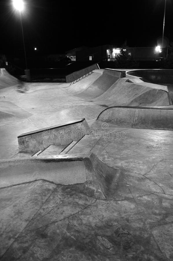 Skatepark At Night. Empty skatepark at night with grind rails. Concrete cement. This is a black and white image royalty free stock photos