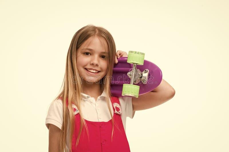 Skater da criança que sorri com longboard Carregado ser uma menina do skater Sorriso pequeno da menina com a placa do patim isola imagens de stock
