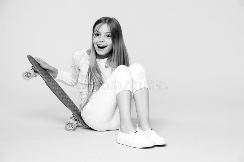 Skater da criança que sorri com longboard A criança do skate senta-se no assoalho Sorriso pequeno da menina com placa do patim no imagem de stock